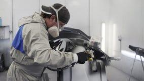 El hombre está pintando piezas del automóvil en la cabina de espray del servicio del coche almacen de metraje de vídeo