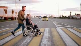 El hombre está quitando a la mujer discapacitada en carro sobre el paso de peatones en ciudad almacen de video