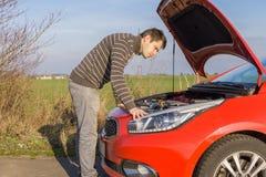 El hombre está reparando el coche roto imagen de archivo libre de regalías