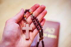 El hombre está rogando: Rosario en las manos, Sagrada Biblia en el fondo imágenes de archivo libres de regalías