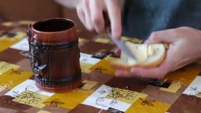 El hombre está separando la mantequilla en un pan al lado de una taza de café caliente metrajes
