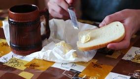 El hombre está separando la mantequilla en un pan al lado de una taza de café caliente almacen de metraje de vídeo