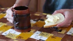El hombre está separando la mantequilla en un pan al lado de una taza de café caliente almacen de video