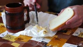 El hombre está separando la mantequilla en un pan al lado de una taza de time lapse caliente del café metrajes