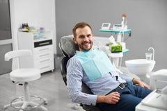 El hombre está sonriendo a la cámara mientras que se sienta en una silla dental en odontología que es feliz y satisfecha con su t foto de archivo