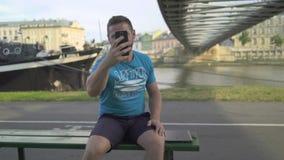 El hombre está sonriendo a la cámara y toma la foto por smatphone metrajes