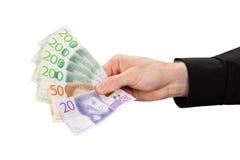El hombre está sosteniendo algunos billetes de banco suecos fotografía de archivo libre de regalías