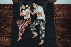 El hombre está sosteniendo el despertador cerca del oído de la mujer en cama fotografía de archivo libre de regalías