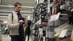 El hombre está sosteniendo en manos un simulador del rodillo del deporte, colocándose en el pasillo de la tienda almacen de video