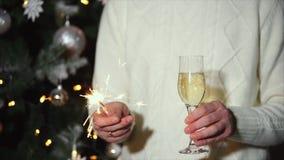 El hombre está sosteniendo la bengala y el vidrio de champán en partido de celebración del Año Nuevo almacen de video