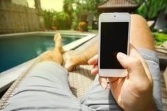 El hombre está sosteniendo su smartphone con una pantalla en blanco en su mano en el fondo de la piscina y sus pies en un deckcha Foto de archivo libre de regalías