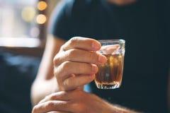 El hombre está sosteniendo té de hielo en su mano Una bebida de restauración Imagenes de archivo