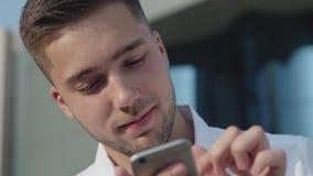 El hombre está sosteniendo un teléfono, mirando en el marco y entonces al teléfono metrajes