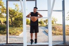 El hombre está sosteniendo una bola de la cesta y está riendo, bola de la calle, competencias de deporte, afro, retrato al aire l Imagen de archivo libre de regalías
