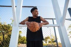 El hombre está sosteniendo una bola de la cesta y está riendo, bola de la calle, competencias de deporte, afro, retrato al aire l Imagen de archivo