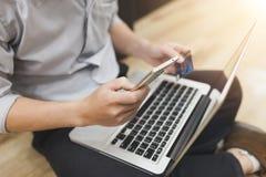 El hombre está sosteniendo una tarjeta de crédito y está utilizando la PC o el ordenador portátil para s en línea Imágenes de archivo libres de regalías