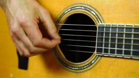 El hombre está tocando la guitarra acústica con una selección metrajes
