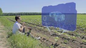 El hombre está trabajando con el coche de carreras 3D en la exhibición olográfica al borde del campo almacen de metraje de vídeo