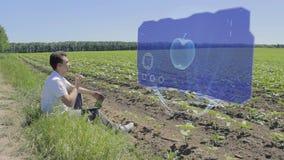 El hombre está trabajando con la manzana 3D en la exhibición olográfica al borde del campo