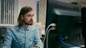 El hombre está trabajando en el ordenador en la oficina como un diseñador o programador almacen de metraje de vídeo