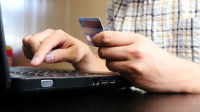 El hombre está utilizando la tarjeta de crédito y el ordenador portátil para el pago en línea almacen de video