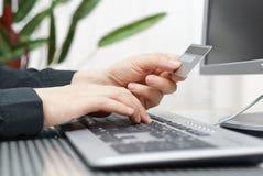 El hombre está utilizando la tarjeta y el ordenador de crédito para en la línea pago Fotos de archivo libres de regalías