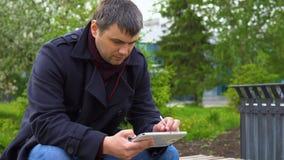 El hombre está utilizando una tableta en el parque almacen de video