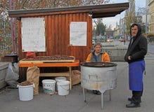 El hombre está vendiendo las castañas asadas en el quiosco en Maribor, Eslovenia imagenes de archivo