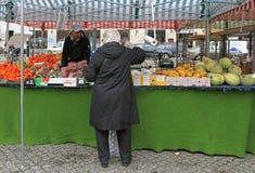 El hombre está vendiendo las frutas y las bayas al aire libre en Malmö, Suecia Imagenes de archivo