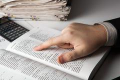 El hombre está buscando la información en el diccionario Fotografía de archivo
