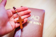 El hombre est? rogando: Rosario en las manos, Sagrada Biblia en el fondo foto de archivo