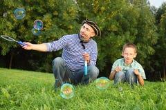El hombre está soplando burbujas de jabón, su hijo está mirando Fotografía de archivo libre de regalías