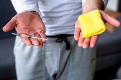 El hombre est? sosteniendo la medicina y una pulsera el concepto de doping en deporte fotografía de archivo