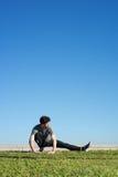 El hombre estira la pierna en la tierra Imágenes de archivo libres de regalías