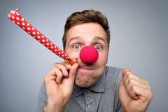 El hombre europeo con la nariz roja del payaso es feliz fotografía de archivo