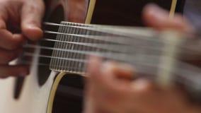 El hombre europeo toca la guitarra en fingerboard