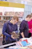 El hombre examina y selecciona los libros Imagenes de archivo