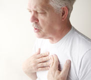 El hombre exhala con las manos en pecho Fotografía de archivo