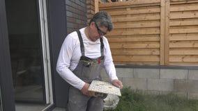 El hombre experto cortó los agujeros en teja usando una amoladora de ángulo almacen de metraje de vídeo