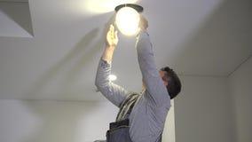 El hombre experto del electricista conecta los alambres con el panel ligero llevado y monta en techo almacen de video