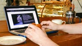 El hombre explora sitio web del espacio X en la pantalla del ordenador portátil en café Fotos de archivo