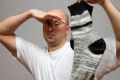 El hombre expresivo está guardando el calcetín del hedor fotografía de archivo