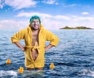 El hombre extraño con el paquete de cara se coloca en agua fotografía de archivo libre de regalías