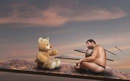 El hombre extraño mira el oso del juguete foto de archivo
