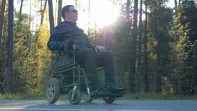 El hombre físicamente desafiado se está sentando en su silla de ruedas accionada al lado del bosque almacen de metraje de vídeo
