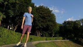 El hombre feliz baila en un parque de protección del medio encintado redondo en el slo-MES almacen de video