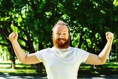 El hombre feliz con la barba roja pone las manos como gesto del éxito Imagen de archivo
