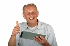 El hombre feliz con los pulgares sube y su ordenador de la tablilla Imagenes de archivo