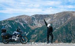 El hombre feliz del motorista está bailando y moto de la aventura en el top de la montaña Viaje de la motocicleta Mundo que viaja fotografía de archivo
