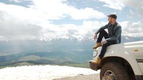 El hombre feliz del viajero que se sienta en su coche en las montañas remata senderismo del viaje 4x4 metrajes